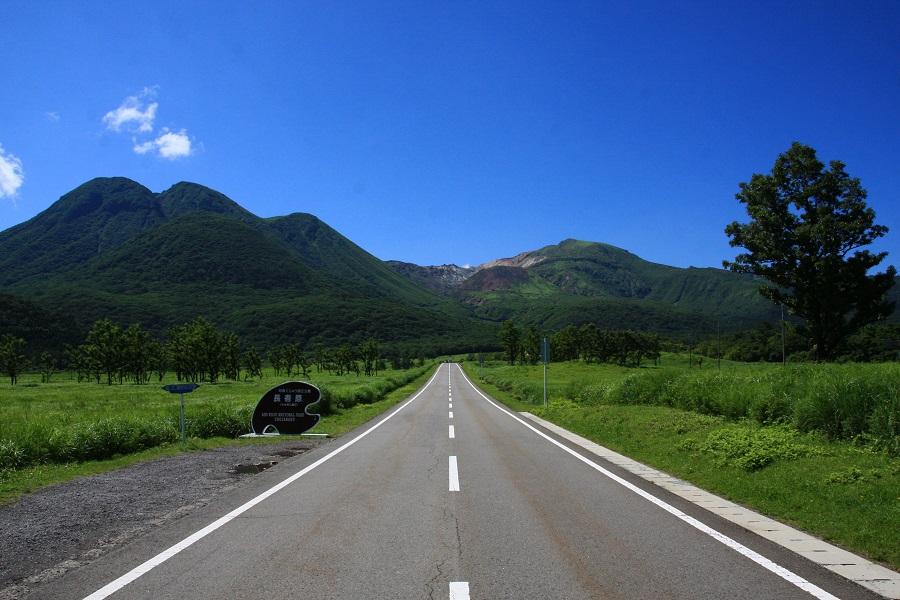 青空と山に続く道路の画像