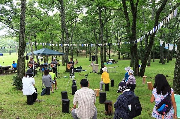野外のフェスで歌う人と観客